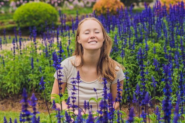 Junge frau auf der oberfläche von blue salvia farinacea blumen, die im garten blühen