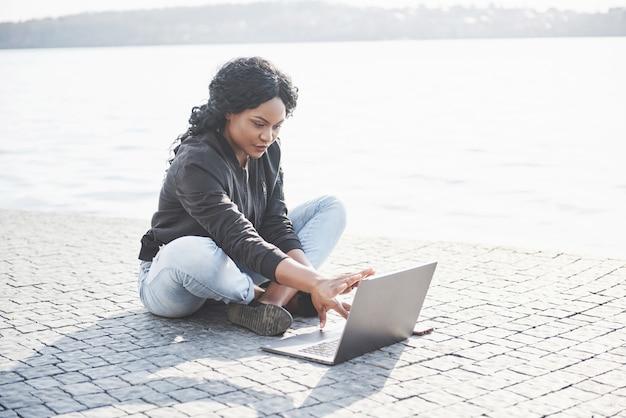 Junge frau auf der straße, die am laptop arbeitet