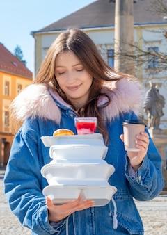 Junge frau auf der straße mit einem mantel mit lunchpaketen und lieferung von kaffee und essen zum mitnehmen.