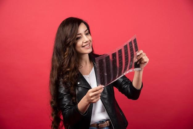 Junge frau auf der suche nach einer datei mit einem fotoband auf rotem grund. foto in hoher qualität