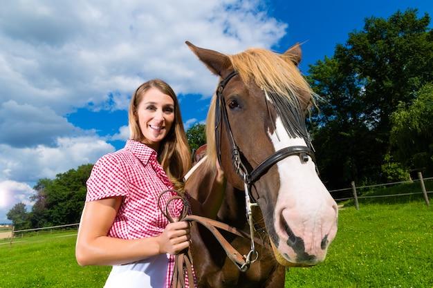 Junge frau auf der wiese mit pferd