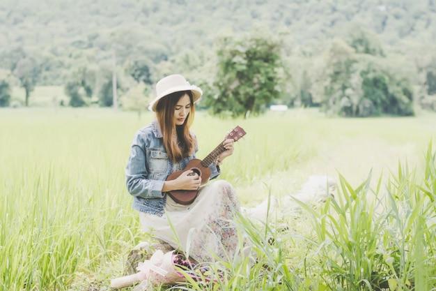Junge frau auf einem gebiet, abgerundeten sonnenbrillen und strohhut und ukulele, die spaß im freien hat.