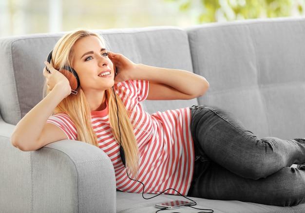 Junge frau auf einem sofa, das musik hört
