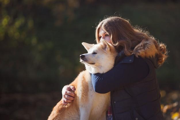 Junge frau auf einem spaziergang mit ihrer hunderasse akita inu