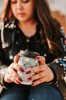 Junge frau auf einer terrasse, die kaffee trinkt