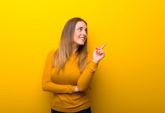 Junge frau auf gelb eine großartige idee zeigend und oben schauend