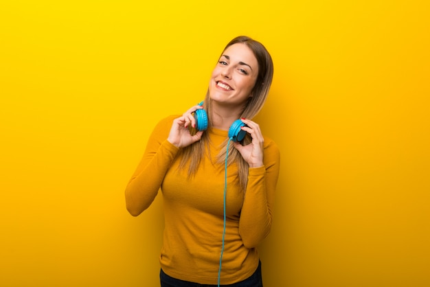 Junge frau auf gelbem hintergrund mit kopfhörern