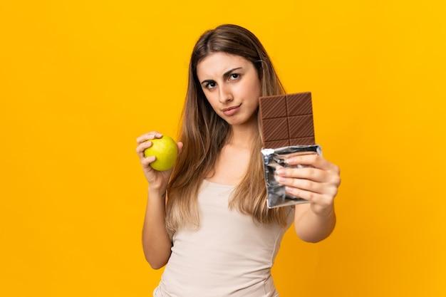 Junge frau auf isoliertem gelb, das eine schokoladentafel in einer hand und einen apfel in der anderen nimmt