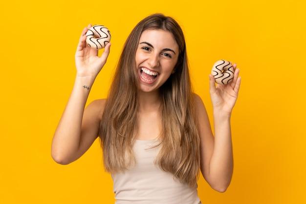 Junge frau auf isolierten gelben haltekrapfen mit glücklichem ausdruck