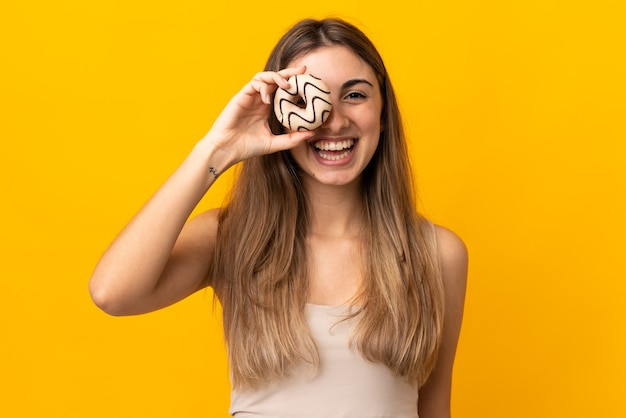 Junge frau auf lokalisiertem gelb, das einen donut hält und glücklich ist