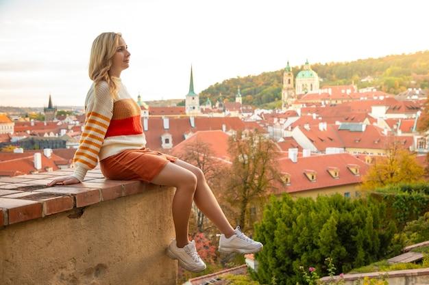 Junge frau auf rotem dachhintergrund in der altstadt von prag in der tschechischen republik