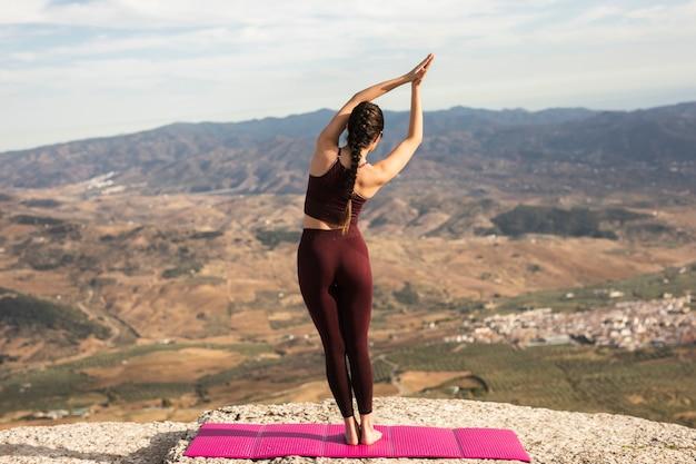 Junge frau auf übendem yoga des berges