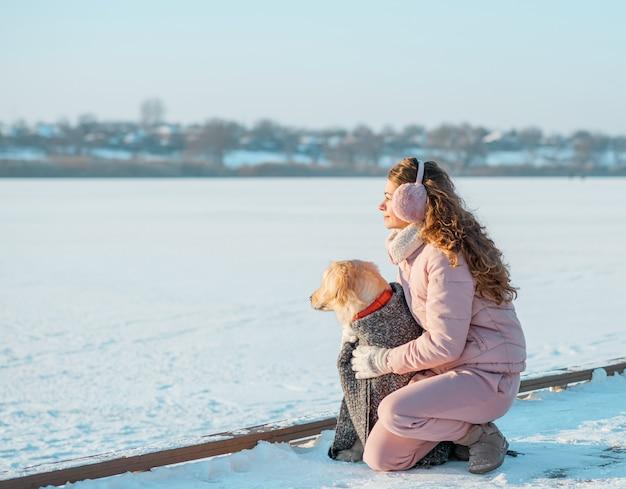 Junge frau auf wintereisfluss, der mit ihrem hund golden retriever sitzt. frau spielt mit hund im freien
