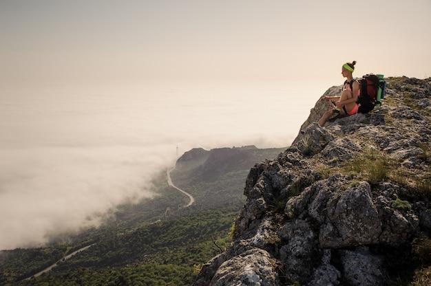 Junge frau backpacker, die auf schönem berggipfelweg wandert.