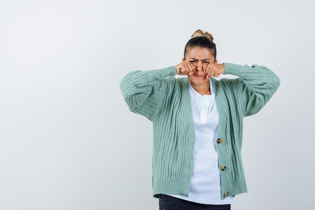 Junge frau ballt fäuste, hält sich an den händen im gesicht, verzieht das gesicht in weißem t-shirt und mintgrüner strickjacke und sieht genervt aus