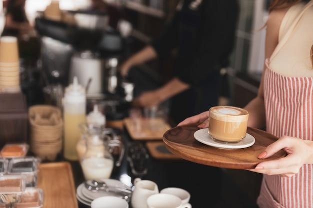 Junge frau barista, die schürze steht, die am kaffeehaus hält tasse hält servierauftrag frische heiße latte am café.