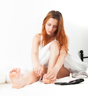 Junge frau behandelt ihre zehennägel zu hause