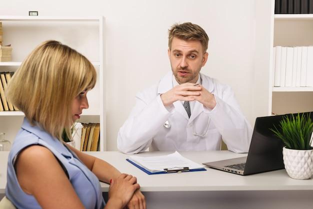 Junge frau bei einer konsultation mit einem männlichen chirurgen oder therapeuten in seinem büro. selektiver fokus auf den arzt.