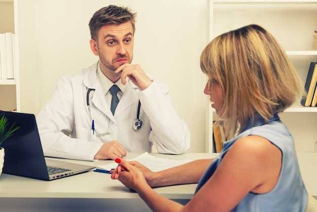 Junge frau bei einer konsultation mit einem männlichen chirurgen oder therapeuten in seinem büro. selektiver fokus auf den arzt