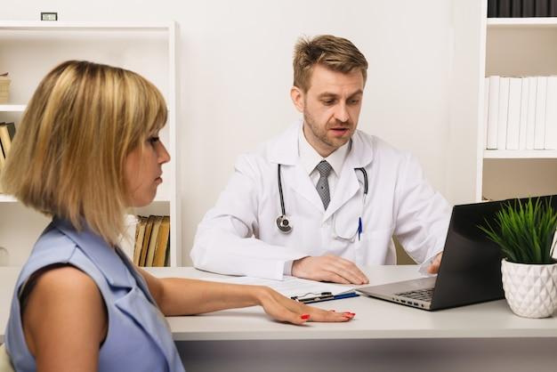 Junge frau bei einer konsultation mit einem männlichen chirurgen oder therapeuten in seinem büro