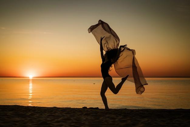 Junge frau bei sonnenuntergang, die an der küste mit einem tuch auf dem hintergrund des himmels springt