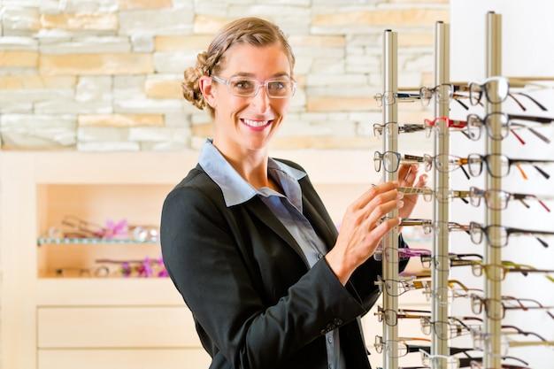Junge frau beim optiker mit brille, sie könnte kunde oder verkäufer sein