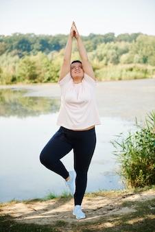 Junge frau beim yoga, umgeben von natur