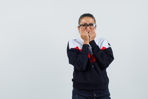 Junge frau beißt fäuste in pullover, schwarzen jeans und brille und sieht ängstlich aus. vorderansicht.