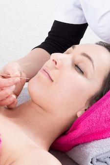 Junge frau bekommt akupunkturbehandlung auf ihrem gesicht von einem chinesischen spezialisten