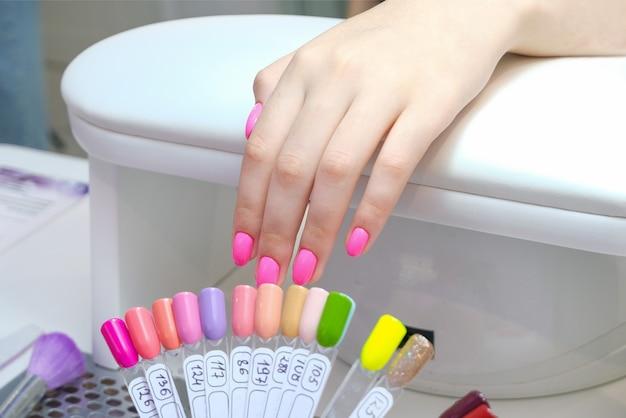 Junge frau bekommt eine maniküre im salon. auftragen von schellack auf die nägel. pinke farbe