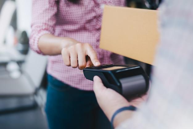 Junge frau benutzt eine kreditkarte, um waren zu bezahlen