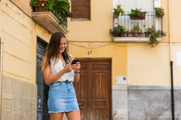 Junge frau benutzt ihren smartphone in der straße