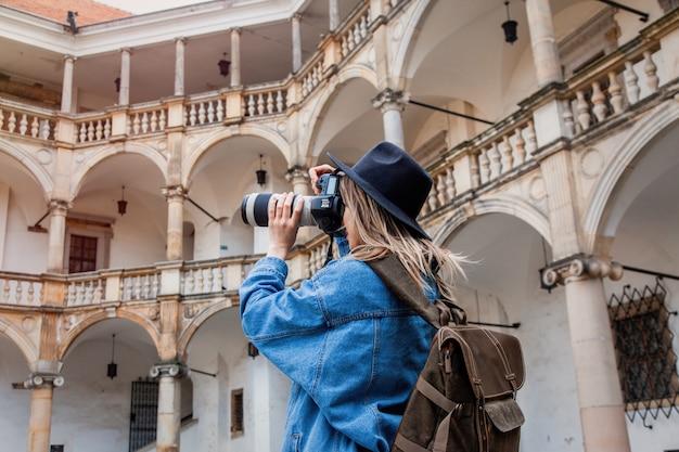 Junge frau, berufsfotograf mit kamera im alten schloss