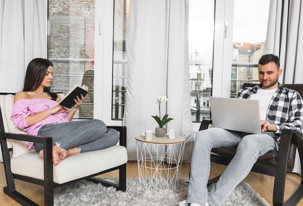 Junge frau beschäftigt beim lesen des buches und ihres freundes, der zu hause laptop verwendet