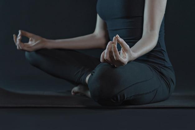 Junge frau beschnitten auf yogamatte, die yoga auf dunklem schwarzem hintergrund praktiziert. speicherplatz kopieren.