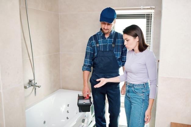 Junge frau beschwert sich beim mechaniker oder techniker über den abfluss in der badewanne oder im rohr und zeigt ihm, wo das problem liegt