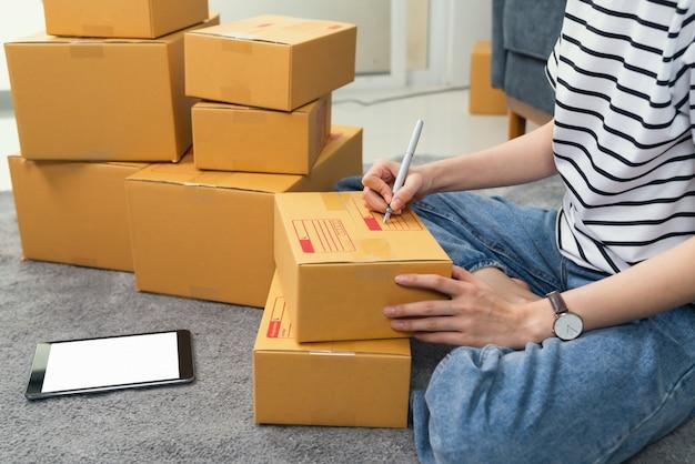 Junge frau besitzerin arbeitet und packt auf box zum kunden am sofa im home office, verkäufer bereitet die lieferung vor.