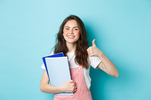 Junge frau besucht kurse, studentin studiert, hält notizbücher und zeigt daumen zur zustimmung, empfiehlt unternehmen, steht auf blauem hintergrund