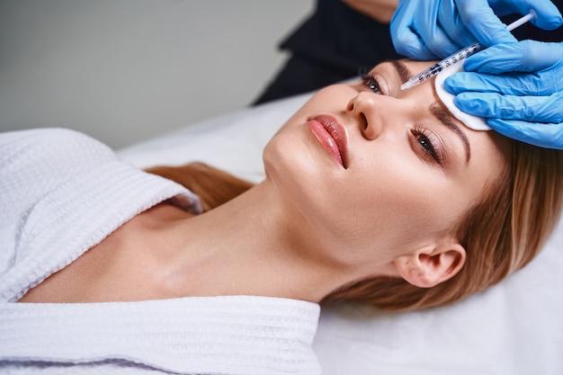 Junge frau beugt altersproblemen vor und besucht kosmetikerin, weil sie botox in die stirn verwendet