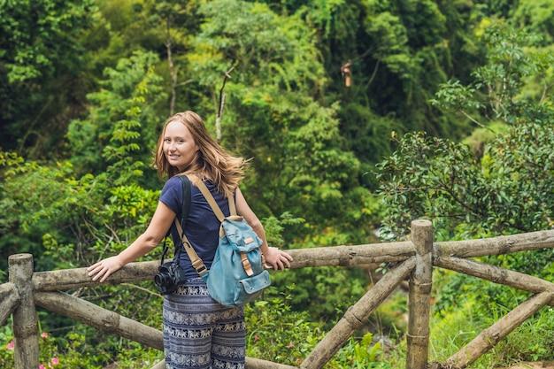 Junge frau bewundert die natur von vietnam durch ländlichen zaun