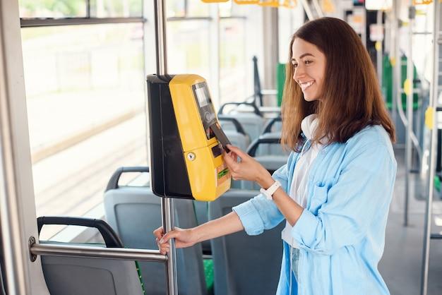 Junge frau bezahlt mit bankkarte für die öffentlichen verkehrsmittel in der straßenbahn oder u-bahn.
