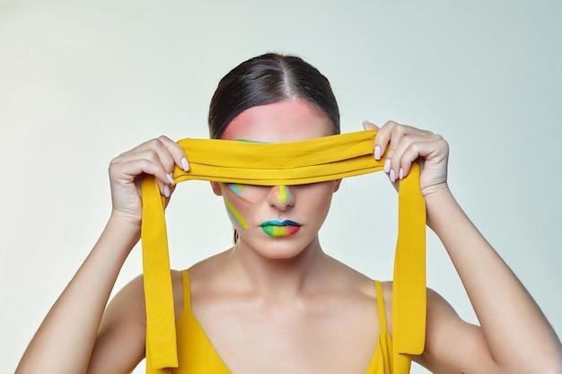 Junge frau bindet ihre augen mit einem gelben band
