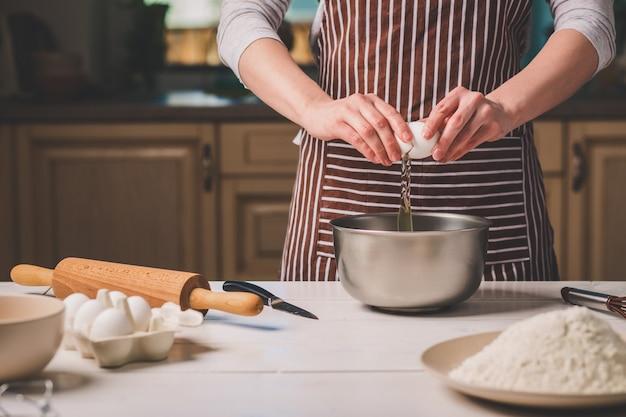 Junge frau bricht ei über schüssel mit teig, nahaufnahme. eine frau in gestreifter schürze kocht in der küche