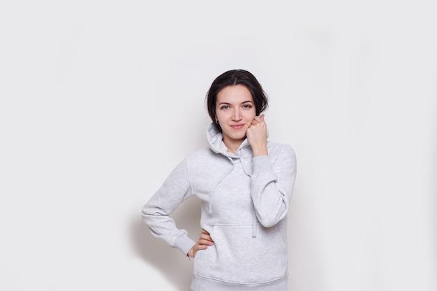 Junge frau brünette in einem hellgrauen pullover mit kapuze, isoliert auf weißem hintergrund, blick in die kamera.