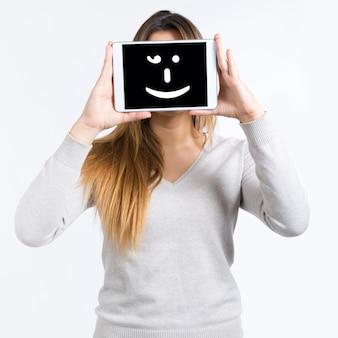 Junge frau deckt ihr gesicht mit digitaler tablette. isoliert auf whit