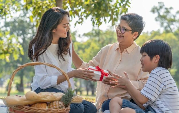 Junge frau der asiatischen familie, die großmutter geschenkbox während des picknicks im park gibt