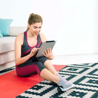 Junge frau der blonden eignung, die auf teppich unter verwendung der digitalen tablette sitzt