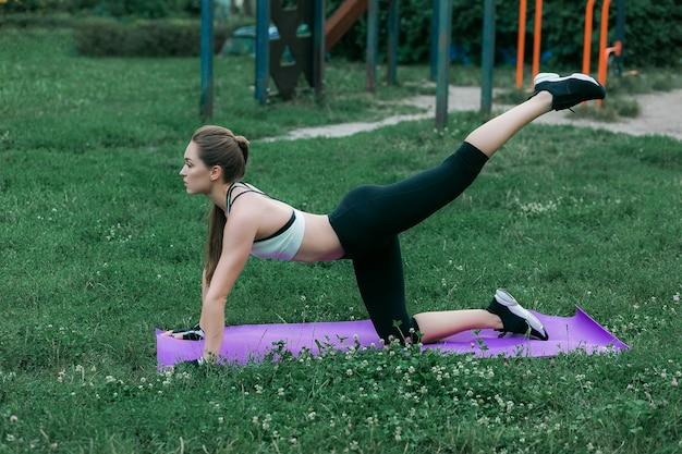 Junge frau der eignung, die im frühjahr park auf purpurroter yogamatte im freien ausübt