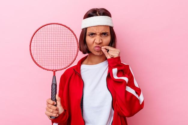 Junge frau der gemischten rasse, die badminton spielt, isoliert auf rosa wand mit den fingern auf den lippen, die ein geheimnis halten.