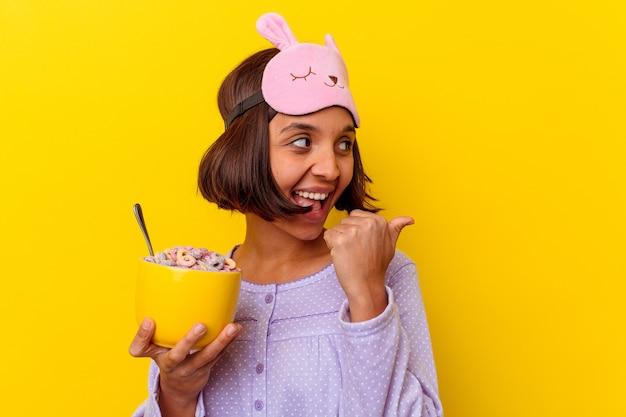 Junge frau der gemischten rasse, die müsli isst, die einen pijama tragen, der auf gelben hintergrundpunkten mit daumenfinger entfernt, lachend und sorglos lokalisiert.